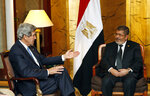 FILE - In this May 25, 2013 file photo, U.S. Secretary of State John Kerry, left, meets with Egyptian President Mohammed Morsi in Addis Ababa, Ethiopia. On Monday June 17, 2019, Egypt's state TV said the country's ousted President Mohammed Morsi, 67, collapsed during a court session and died. It said it occurred while he was attending a court trial on Monday on espionage charges. Morsi, who hailed from Egypt's largest Islamist group, the now outlawed Muslim Brotherhood, was elected president in 2012 in the country's first free elections following the ouster the year before of longtime leader Hosni Mubarak. (AP Photo/Jim Young, Pool, File)