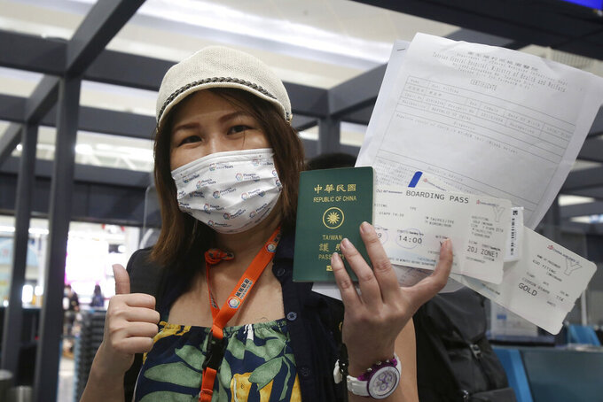 Taiwanese traveler Kuo Yitting of the first group of Palau-Taiwan Travel Corridor shows her boarding pass and a report of virus antigen test before leaving Taiwan, at Taoyuan International Airport in Taoyuan, northern Taiwan, Thursday, April 1, 2021. The Palau-Taiwan Travel Corridor, allowing people to travel between the islands without a COVID-19 quarantine, has started Thursday. (AP Photo/Chiang Ying-ying)