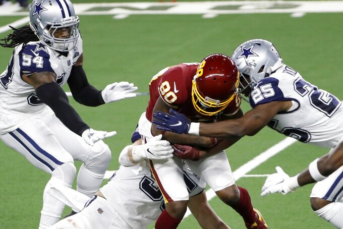 Dallas Cowboys' Jaylon Smith (54), Leighton Vander Esch, bottom left, and Xavier Woods (25) combine to stop Washington Football Team wide receiver Dontrelle Inman (80) from gaining extra yardage after catching a pass in the second half of an NFL football game in Arlington, Texas, Thursday, Nov. 26, 2020. (AP Photo/Roger Steinman)