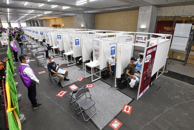 FILE - In this May 31, 2021, file photo, people receive the Pfizer COVID-19 vaccine at the Noevir Stadium Kobe in Kobe, western Japan.  (Yu Nakajima/Kyodo News via AP, File)