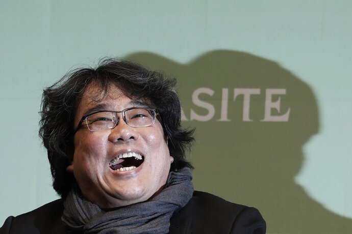 """Bong Joon-ho, director of Oscar-winning """"Parasite,"""" laughs during a press conference in Seoul, South Korea, Wednesday, Feb. 19, 2020. Bong said Wednesday """"the biggest pleasure and the most significant meaning"""" that the film has brought to him was its success in many countries though the audiences might feel uncomfortable with his explicit description of a bitter wealth disparity in modern society. (AP Photo/Ahn Young-joon)"""
