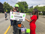 FILE - In this Thursday, June 20, 2019, file photo, a TV reporter interviews self-employed logger Bridger Hasbrouck, of Dallas, Ore., outside the Oregon State House in Salem, Ore. The stark divide in Oregon between the state's liberal, urban population centers and its conservative and economically depressed rural areas makes it fertile ground for the partisan crisis currently unfolding there. Rural voters worry the cap-and-trade bill would be the end for logging and trucking.