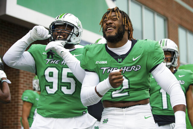 Marshall's Darius Hodge (2) and Kyron Taylor (95) talk with friends in the stands as they prepare to take on Florida Atlantic during an NCAA football game on Saturday, Oct. 24, 2020, at Joan C. Edwards Stadium Huntington, W.Va. (Sholten Singer/The Herald-Dispatch via AP)