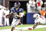 Mississippi quarterback Matt Corral (2) runs past Austin Peay's Jau'von Young (3) during an NCAA college football game in Oxford, Miss., Saturday, Sept. 11, 2021. (AP Photo/Bruce Newman)