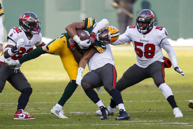 Green Bay Packers' Aaron Jones is tackled by Tampa Bay Buccaneers' Devin White (45) during the first half of the NFC championship NFL football game in Green Bay, Wis., Sunday, Jan. 24, 2021. (AP Photo/Matt Ludtke)
