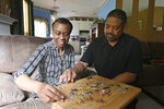 Robert Reid helps his wife Kim Reid, who was diagnosed with early-onset Alzheimer's, as she puts a puzzle together at their home in Hampton on Thursday, June 10, 2021.  (Hyosub Shin/Atlanta Journal-Constitution via AP)