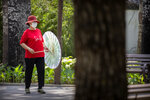 A woman wearing a face mask to protect against the new coronavirus dances with a parasol at a public park in Beijing, Wednesday, June 10, 2020. China says its three latest cases of coronavirus infection were brought from outside the country. No new deaths were reported Wednesday and just a few dozen people remain in treatment for COVID-19. (AP Photo/Mark Schiefelbein)