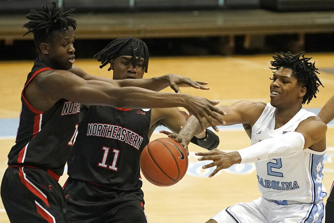 Northeastern forward Greg Eboigbodin, left, and guard Jahmyl Telfort (11) struggle with North Carolina guard Caleb Love (2) for possession of the ball during the first half of an NCAA college basketball game in Chapel Hill, N.C., Wednesday, Feb. 17, 2021. (AP Photo/Gerry Broome)