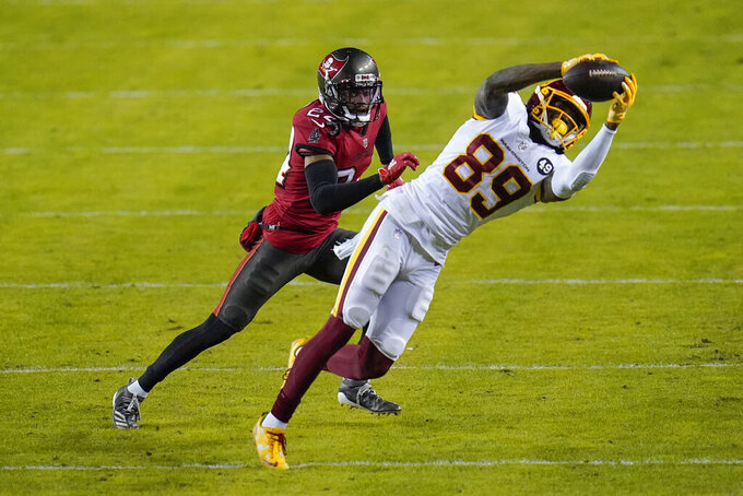 Washington Football Team wide receiver Cam Sims (89) makes a catch against Tampa Bay Buccaneers cornerback Carlton Davis (24) during the first half of an NFL wild-card playoff football game, Saturday, Jan. 9, 2021, in Landover, Md. (AP Photo/Julio Cortez)