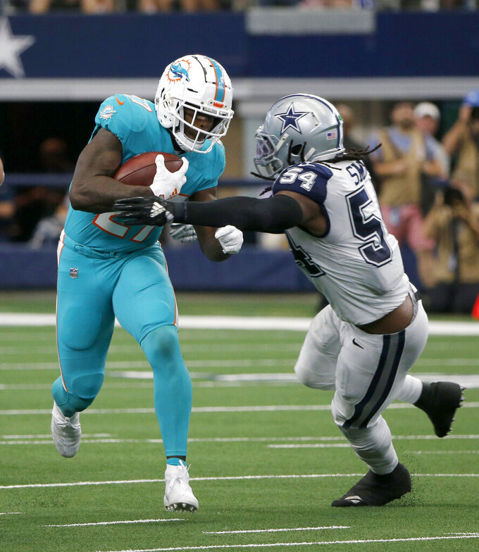 Miami Dolphins running back Kalen Ballage (27) struggles for extra yardage as Dallas Cowboys middle linebacker Jaylon Smith (54) makes the stop in the second half of an NFL football game in Arlington, Texas, Sunday, Sept. 22, 2019. (AP Photo/Michael Ainsworth)
