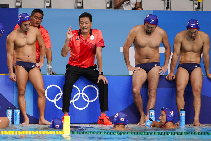 Japan's head coach Yoji Omoto talks with his team during a preliminary round men's water polo match against the United States at the 2020 Summer Olympics, Sunday, July 25, 2021, in Tokyo, Japan. (AP Photo/Mark Humphrey)