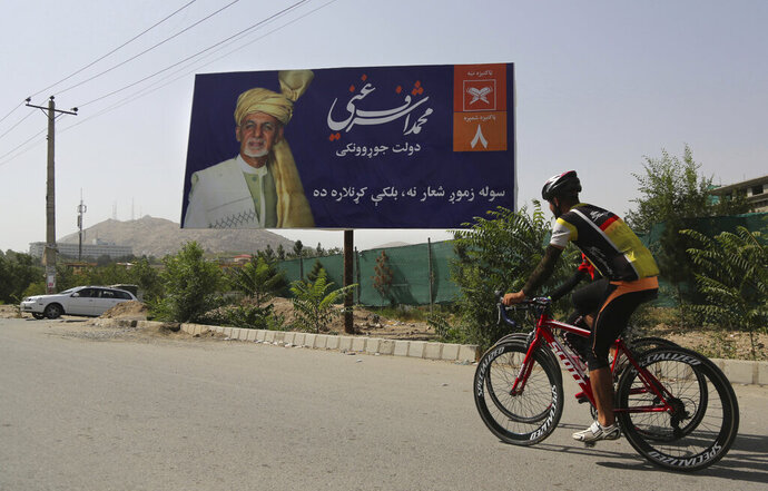 Afghan men rides cycle past an election hoarding of a presidential candidate Ashraf Ghani in Kabul,Afghanistan Friday, Aug. 9, 2019.Afghanistan faces a presidential election next month but few believe the vote will take place as the United States and the Taliban inch closer to a deal that could end the nearly 18-year war but bring uncertainty about almost everything else. (AP Photo/Nishanuddin Khan)