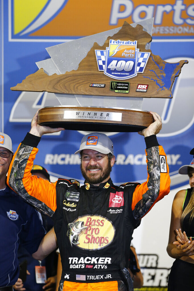Martin Truex Jr. holds the trophy after winning the NASCAR Cup Series auto race at Richmond Raceway in Richmond, Va., Saturday, Sept. 21, 2019. (AP Photo/Steve Helber)