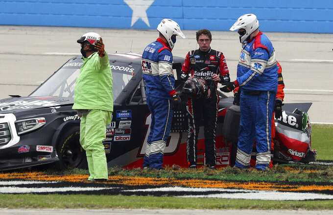 Officials tend to NASCAR Texas Trucks Series driver Christian Eckes (18) after he skidded out on the front stretch after contact from another vehicle during an auto race at Texas Motor Speedway in Fort Worth, Texas, Sunday, Oct. 25, 2020. (AP Photo/Richard W. Rodriguez)