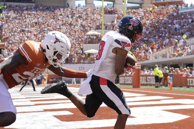 Texas Tech wide receiver Myles Price (18) catches a touchdown pass against Texas defensive back B.J. Foster (25) during the first half of an NCAA college football game on Saturday, Sept. 25, 2021, in Austin, Texas. (AP Photo/Chuck Burton)