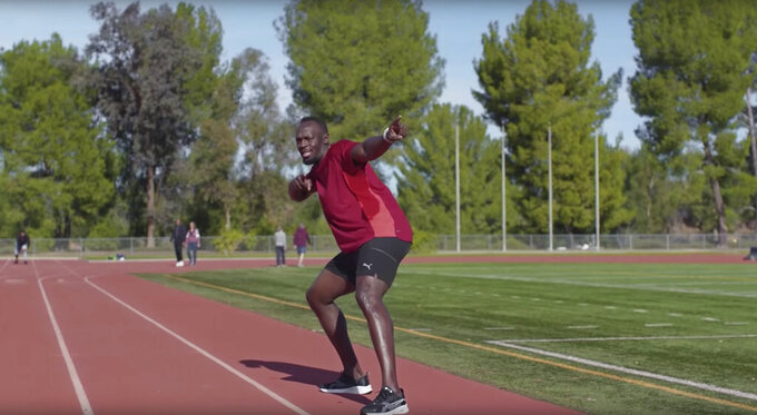 """This undated image provided by Michelob ULTRA shows Usain Bolt in a scene from the company's 2020 Super Bowl NFL football spot. Wrestler-turned-actor John Cena tries to convince Tonight Show host Jimmy Fallon that there's a """"lighter side"""" to working out, with cameos by Tonight show band The Roots and runner Usain Bolt. (Michelob ULTRA via AP)"""