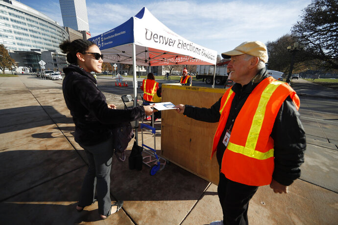 Voter Hannah Johnson, left, hands her ballot to election judge Michael Michalek at pick-up site of the Denver Election Division outside the City/County Building early Tuesday, Nov. 5, 2019, in Denver. (AP Photo/David Zalubowski)