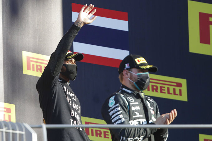Mercedes driver Lewis Hamilton of Britain, left, celebrates on the podium next to Mercedes driver Valtteri Bottas of Finland after winning the Formula One Grand Prix of Tuscany, at the Mugello circuit in Scarperia, Italy, Sunday, Sept. 13, 2020. (AP Photo/Luca Bruno, Pool)