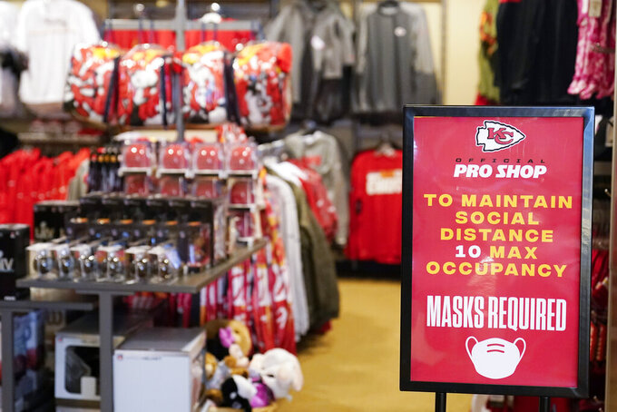 A sign reminds shoppers to keep social distance and wear masks in at souvenir shop at Arrowhead Stadium before an NFL football game between the Kansas City Chiefs and the Houston Texans Thursday, Sept. 10, 2020, in Kansas City, Mo. (AP Photo/Jeff Roberson)