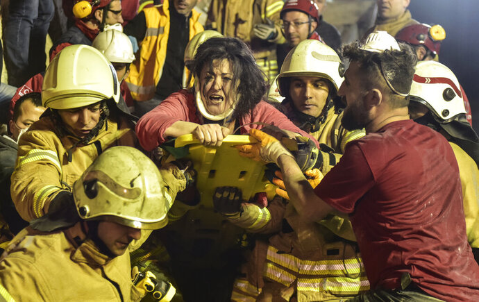 A woman reacts after rescue workers had pulled her out the rubble of an eight-story building which collapsed in Istanbul, Wednesday, Feb. 6, 2019. The eight-story building collapsed, killing at least two people and trapping several others inside the rubble, Turkish officials said. The building had 43 people living in 14 apartments, with a street-level ground floor and seven higher floors, Istanbul Gov. Ali Yerlikaya said, adding that the top three floors had been built illegally. (DHA via AP)