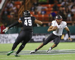 UNLV quarterback Armani Rogers (1) slides away from Hawaii defensive lineman Manly Williams (49) during the second quarter of an NCAA college football game, Saturday, Nov. 17, 2018, in Honolulu. (AP Photo/Marco Garcia)