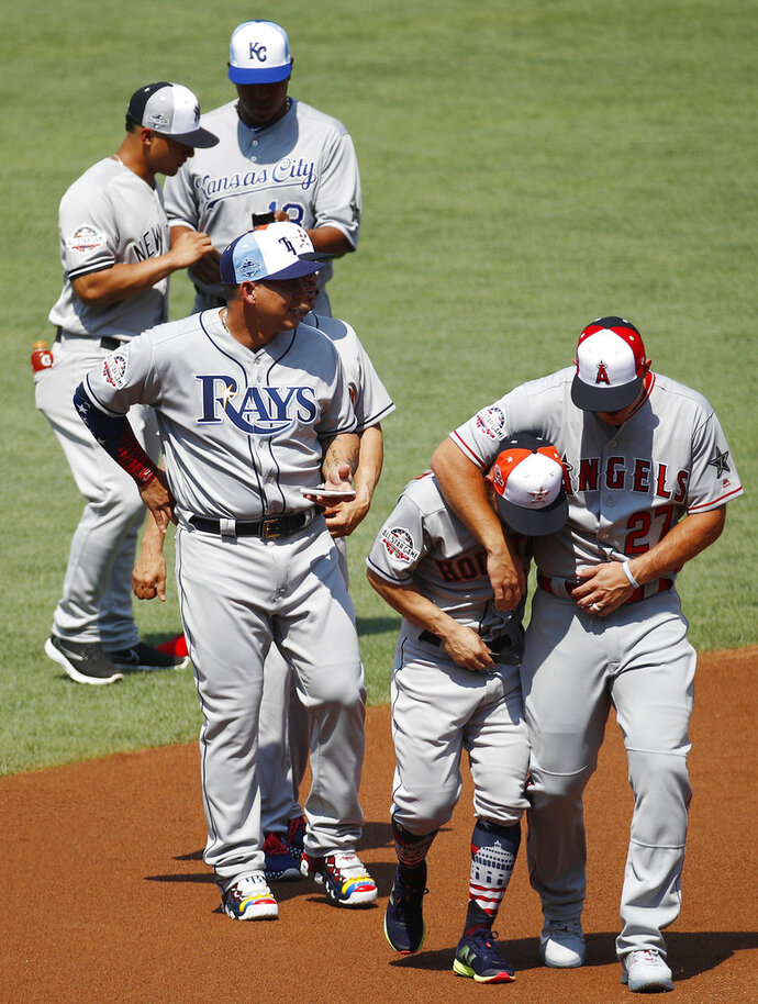 CORRECTS TO JOSE ALTUVE NOT ALEX BREGMAN - American League, Houston Astros' Jose Altuve, second from right, walks with National League, Los Angeles Angels' Mike Trout, right, after a team photo, Monday, July 16, 2018, at Nationals Park, in Washington. The the MLB baseball All-Star Game will be played Tuesday. (AP Photo/Patrick Semansky)