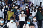 Office workers wearing face masks to help curb the spread of the coronavirus head to worlplaces in Bangkok, Thailand, Thursday, May 21, 2020. Thai health officials say scientists in Thailand have had promising results in testing a COVID-19 vaccine candidate on mice, and will begin testing it on monkeys next week.(AP Photo/Sakchai Lalit)
