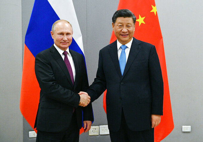 "FILE - In this Nov. 12, 2019, file photo, Russian President Vladimir Putin, left, and China's President Xi Jinping shake hands prior to their talks on the sideline of the 11th edition of the BRICS Summit, in Brasilia, Brazil. Putin and Xi have developed strong personal ties helping bolster a ""strategic partnership"" between the two former Communist rivals. (Ramil Sitdikov/Sputnik, Kremlin/Pool Photo via AP, File)"