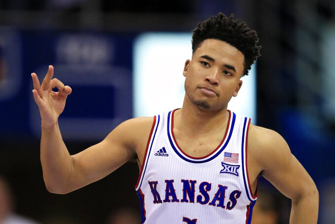 """FILE - In this March 4, 2020, file photo, Kansas guard Devon Dotson celebrates a 3-point basket during the second half of the team's NCAA college basketball game against TCU in Lawrence, Kan. Dotson is entering the NBA draft after leading the Big 12 Conference in scoring his sophomore season. """"In basketball, this has always been my ultimate dream and my time at KU has prepared me,"""" Dotson said Monday, April 13, 2020, in a news release.(AP Photo/Orlin Wagner, File)"""