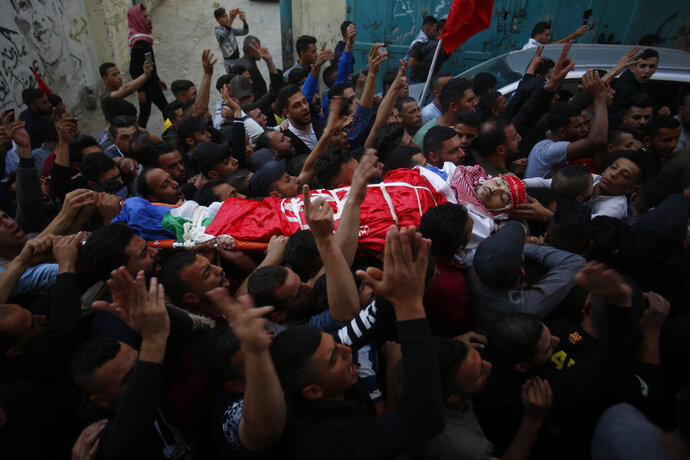 Palestinian mourners carry the body of Omar Badawi, 22, during his funeral at the al-Arroub refugee camp in the West Bank city of Hebron, Monday, Nov. 11, 2019. Badawi was shot in the chest during the confrontation with Israeli forces in the Aroub refugee camp, near the city of Hebron, on Monday afternoon. It gave no further details.(AP Photo/Majdi Mohammed)