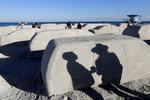 People walk among cars sculpted in sand stuck in a traffic jam, titled Order of Importance by artist Leandro Erlich, as part of Miami Art Week, Tuesday, Dec. 3, 2019, in Miami Beach, Fla. Erlich was commissioned by the city of Miami Beach to create the work, which was unveiled during Art Basel Miami. (AP Photo/Lynne Sladky)