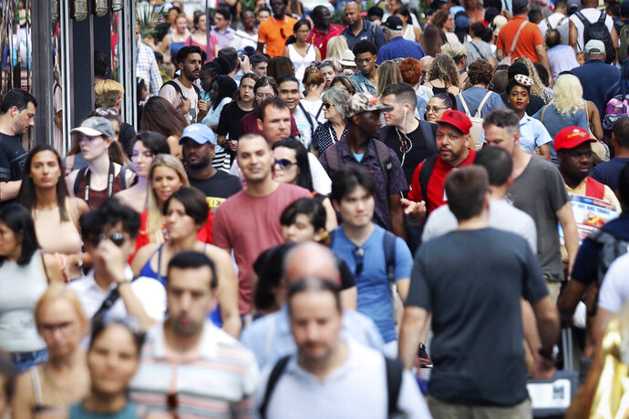 FILE - In this Aug. 22, 2019, file photo, people walk through New York's Times Square. The population of non-Hispanic whites in the U.S. has gotten smaller in the past decade as deaths have surpassed births in this aging demographic, and a majority of the population under age 16 is nonwhite for the first time though they are fewer in number than a decade ago, according to new figures released Thursday, June 25, 2020,  by the U.S. Census Bureau. (AP Photo/Bebeto Matthews, File)