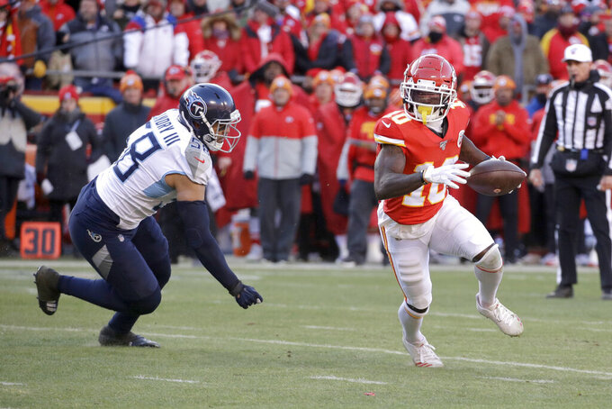 Kansas City Chiefs wide receiver Tyreek Hill (10) runs away from Tennessee Titans linebacker Harold Landry III (58) during the first half of the NFL AFC Championship football game Sunday, Jan. 19, 2020, in Kansas City, MO. (AP Photo/Charlie Riedel)