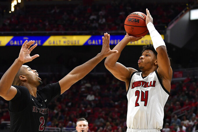 Louisville forward Dwayne Sutton (24) attempts to shoott over the defense of North Carolina Central forward Jibri Blount (2) during the second half of an NCAA college basketball game in Louisville, Ky., Sunday, Nov. 17, 2019. (AP Photo/Timothy D. Easley)