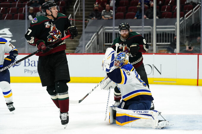 St. Louis Blues goaltender Jordan Binnington (50) makes a save in front of Arizona Coyotes center Tyler Pitlick (17) in the second period during an NHL hockey game, Friday, Feb. 12, 2021, in Glendale, Ariz. (AP Photo/Rick Scuteri)