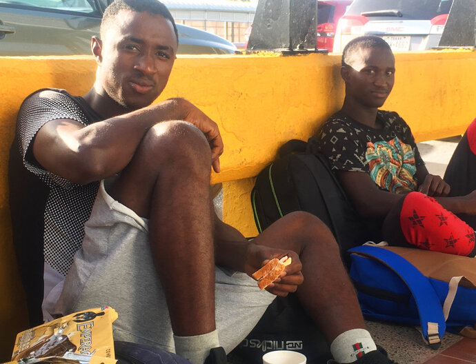 In this July 3, 2018 photo, Mamadou Aliou Barry, left, departed from his native Guinea in West Africa when he was 14, a few years ago, waits for entry to the U.S. on the Gateway Bridge in Matamoros, Mexico, which connects to Brownsville, Texas. He said as part of the minority ethnic Fula group, he fears for his life and carries prints of a picture of him and a friend together and a picture of his friend after he was murdered, for his asylum interview. (AP Photo/Emily Schmall)