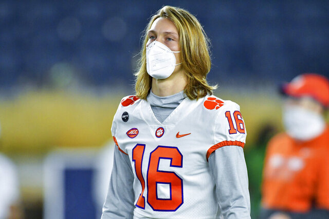 Clemson quarterback Trevor Lawrence watches players warm up for an NCAA college football game between Clemson and Notre Dame on Saturday, Nov. 7, 2020, in South Bend, Ind. (Matt Cashore/Pool Photo via AP)