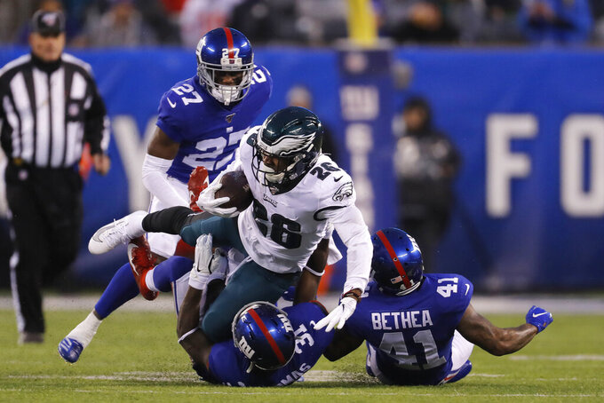 Philadelphia Eagles running back Miles Sanders (26) is stopped by New York Giants free safety Antoine Bethea (41) and New York Giants defensive back Michael Thomas (31) in the first half of an NFL football game, Sunday, Dec. 29, 2019, in East Rutherford, N.J. (AP Photo/Adam Hunger)