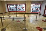 Pedestrians pass the Online Order Pickup area at the Macy's Herald Square location Friday, June 19, 2020, in New York. As Macy's and other retailers reopen their doors, shoppers face an entirely new experience. (AP Photo/Frank Franklin II)