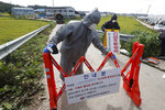 FILE - In this Sept. 17, 2019, file photo, quarantine officials wearing protective gears place barricades as a precaution against African swine fever at a pig farm in Paju, South Korea. Amid swine fever scare that grips both Koreas, South Korea on Tuesday, Oct. 15, is deploying snipers, installing traps and flying drones along the rivals' tense border to kill wild boars that some experts say may have spread the animal disease from north to south. The notice reads: