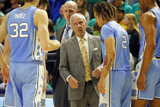 North Carolina head coach Roy Williams, center, talks with his team during a timeout during the second half of an NCAA college basketball game against North Carolina Wilmington in Wilmington, N.C., Friday, Nov. 8, 2019. (AP Photo/Karl B DeBlaker)