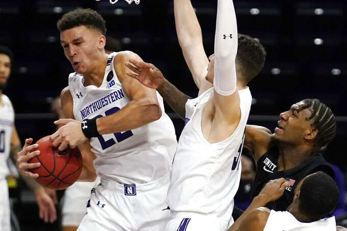 Northwestern forward Pete Nance, left, rebounds the ball against forward Robbie Beran, center, and Michigan State forward Aaron Henry during the first half of an NCAA college basketball game in Evanston, Ill., Sunday, Dec. 20, 2020. (AP Photo/Nam Y. Huh)
