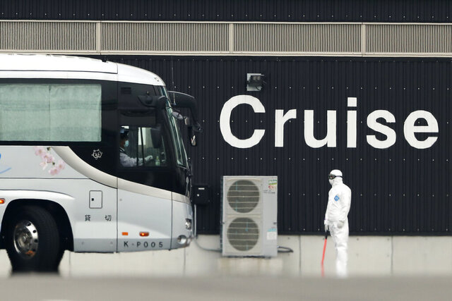 A bus carrying the passengers from the quarantined Diamond Princess cruise ship prepares to leave a port in Yokohama, near Tokyo, Thursday, Feb. 20, 2020. The cruise ship started letting passengers who tested negative for the virus leave the ship Wednesday. Test results are still pending for some people on board. (AP Photo/Eugene Hoshiko)