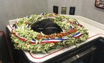 Indianapolis 500 champion Simon Pagenaud's wreath he won less than a week ago is seen Friday, May 31, 2019 in Detroit. Pagenaud lamented seeing the leaves and orchids wilting. At the doubleheader in Detroit, the IndyCar points leaders is looking for a way to preserve his coveted prize and is energized to stay on top of the series. (AP Photo/Larry Lage)