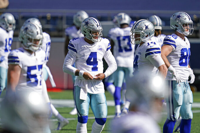 Dallas Cowboys quarterback Dak Prescott (4) stands with teammates on the field before an NFL football game against the Seattle Seahawks, Sunday, Sept. 27, 2020, in Seattle. (AP Photo/Elaine Thompson)