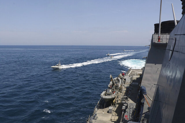 In this Wednesday, April 15, 2020, photo made available by U.S. Navy, Iranian Revolutionary Guard vessels sail close to U.S. military ships in the Persian Gulf near Kuwait. A group of 11 Iranian naval vessels made