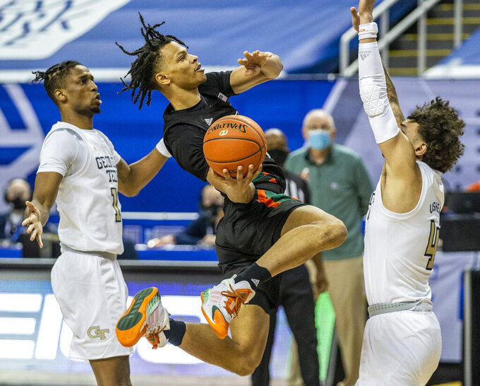 Miami's Isaiah Wong, center, puts up a shot against Georgia Tech during an NCAA college basketball game in the quarterfinal round of the Atlantic Coast Conference tournament in Greensboro, N.C., Thursday, March 11, 2021. (Woody Marshall/News & Record via AP)