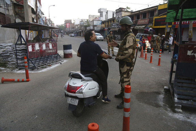 An Indian paramilitary soldier stops a commuter during curfew like restrictions in Jammu, India, Monday, Aug. 5, 2019. An indefinite security lockdown was in place in the Indian-controlled portion of divided Kashmir on Monday, stranding millions in their homes as authorities also suspended some internet services and deployed thousands of fresh troops around the increasingly tense region. (AP Photo/Channi Anand)