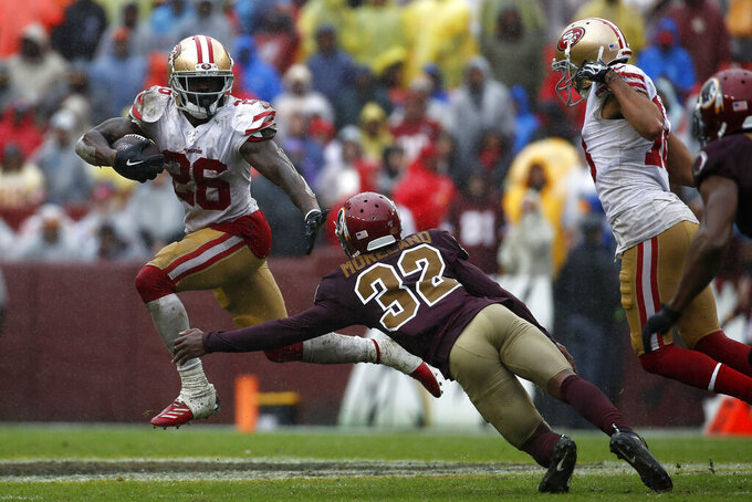 San Francisco 49ers running back Tevin Coleman, left, rushes past Washington Redskins cornerback Jimmy Moreland in the second half of an NFL football game, Sunday, Oct. 20, 2019, in Landover, Md. (AP Photo/Alex Brandon)