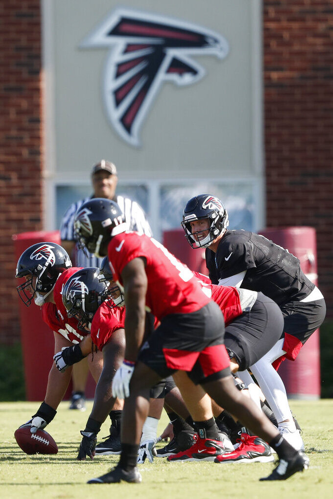 FILE - In this July 25, 2019, file photo, Atlanta Falcons quarterback Matt Ryan (2) and the offense prepare to run a play during their NFL training camp football practice in Flowery Branch, Ga. The Atlanta Falcons shut their facility Thursday, Oct. 15, 2020, following one new positive test for COVID-19. The team remains scheduled to play at Minnesota on Sunday. (AP Photo/John Bazemore, File)